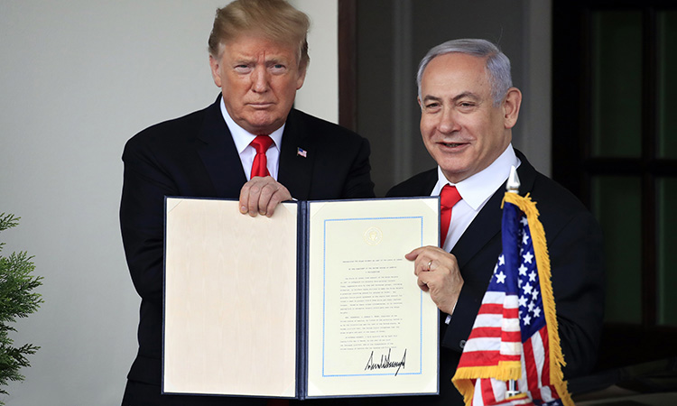 Israeli Prime Minister Benjamin Netanyahu and President Donald Trump hold up the signed proclamation recognizing Israel's sovereignty over the Golan Heights as Netanyahu leaves the White House in Washington, Monday, March 25, 2019.